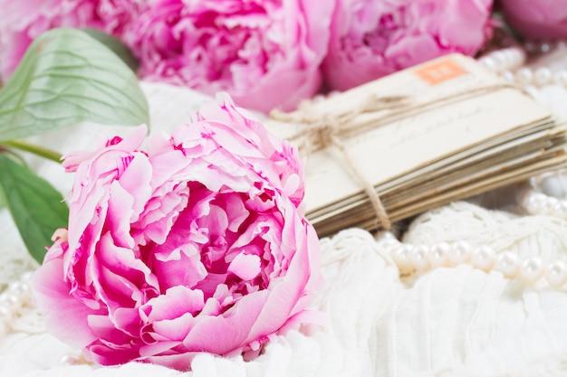 Свежие розовые пионы с кучей старой почты на белом кружеве