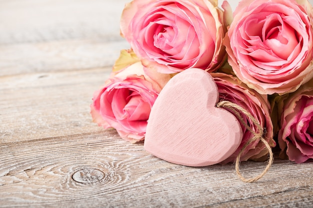 Fresh pink roses and heart decoration on wooden boards