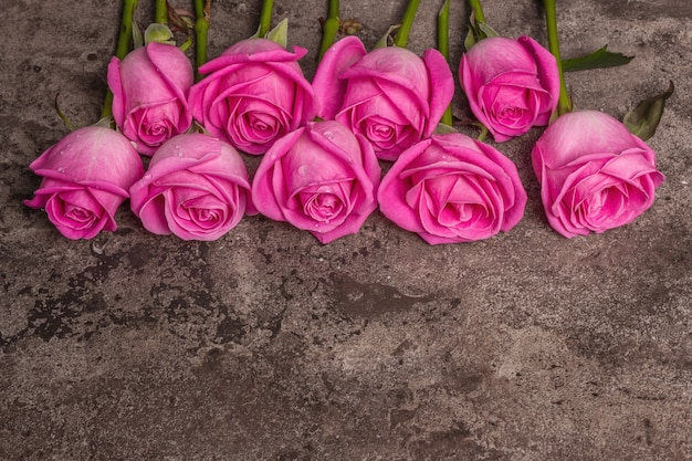 Fresh pink roses on textured stone concrete background. greeting card for weddings, birthdays, march 8th, mother's, or valentine's day