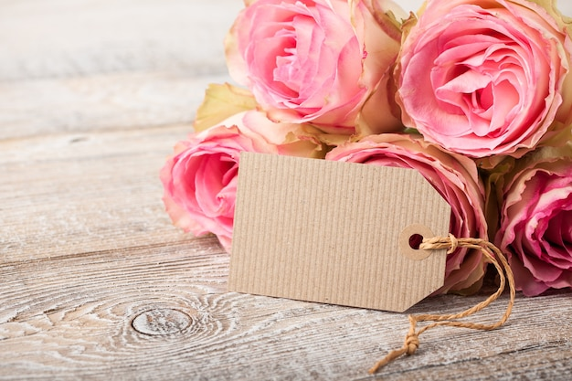 Fresh pink roses with paper tag for greeting on wooden boards