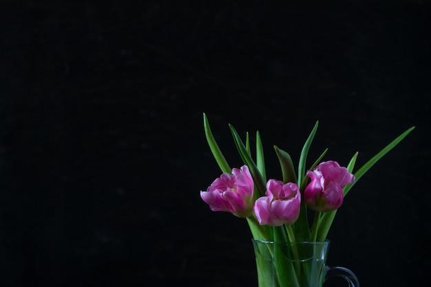 暗い背景にガラスの瓶に新鮮なピンクのチューリップの花の花束