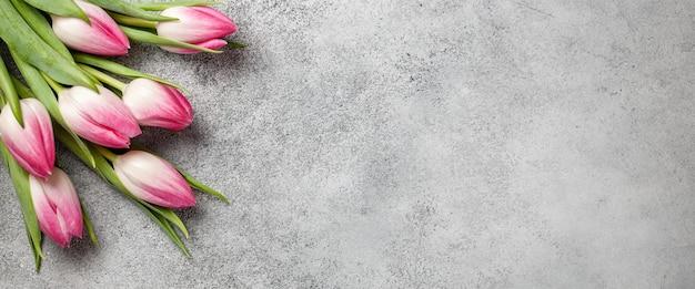 회색 돌 표면에 신선한 핑크 튤립