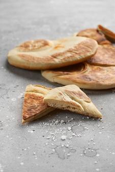 石のテーブルの上の新鮮なピタ。地中海料理の伝統料理。