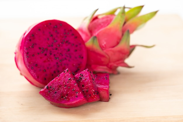 Fresh pitahaya fruit sliced on wooden background or ripe dragon fruit red color with copy-space