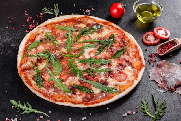 Fresh pizza baked in oven with arugula, salami, cherry tomatoes and mozzarella. italian cuisine