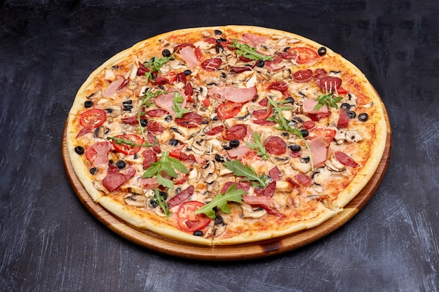 Fresh pizza campania on wooden cutting board. isolated on dark background.