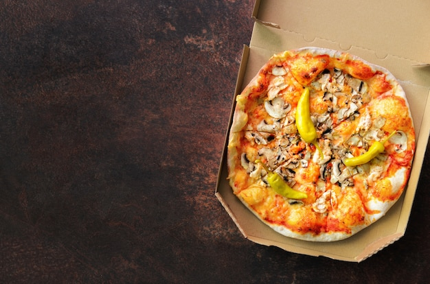 Fresh pizza in delivery box on dark concrete background.