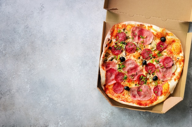 Fresh pizza in delivery box on grey concrete background. top view, copy space