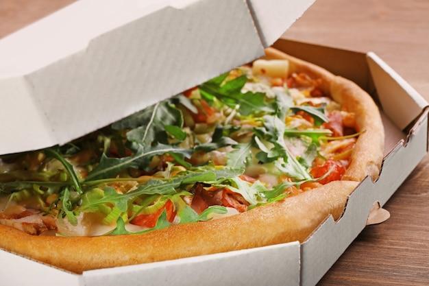 木製のテーブルのクローズアップの段ボール箱で新鮮なピザ