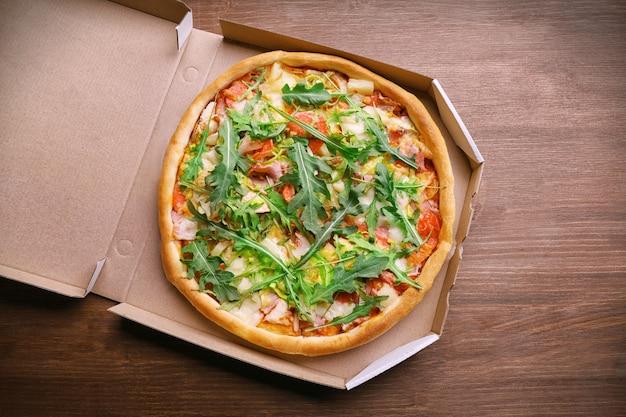 木製のテーブル、上面図のカートンボックスで新鮮なピザ