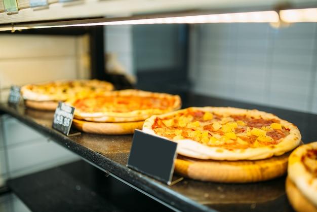 Fresh pizza on shelf in food store closeup, nobody. empty price, traditional italian cuisine in market