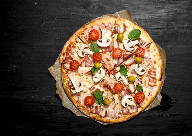ベーコン、トマト、オリーブ、グリーンのフレッシュピザ。黒い黒板に。