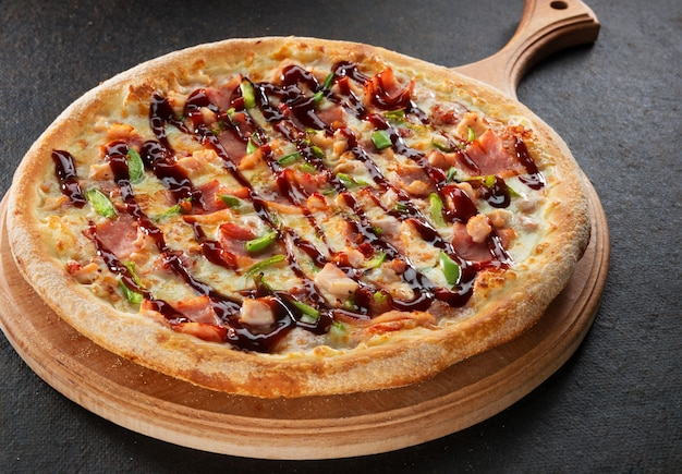 Fresh pizza with bbq sauce on wooden cutting board