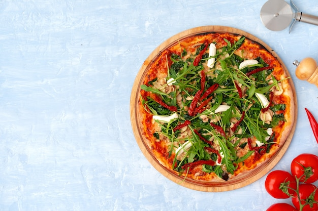 회색 테이블에 허브와 태양 건조 토마토와 신선한 피자