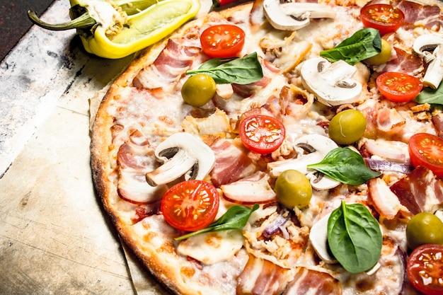 Свежая пицца с грибами, беконом и помидорами. на деревенском фоне.