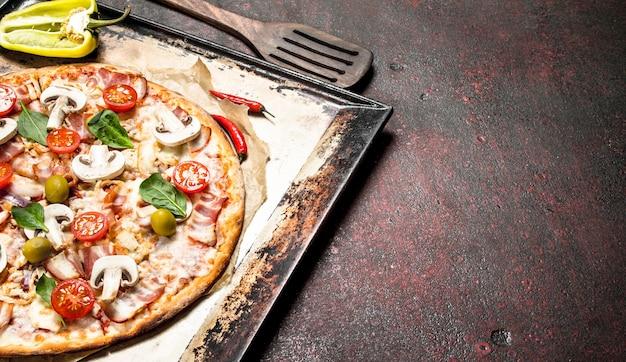 Свежая пицца с грибами, беконом и помидорами. .