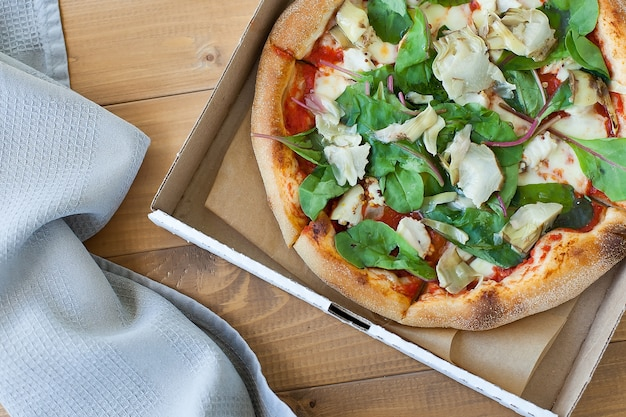 Свежая пицца с помидорами, сыром и грибами на крупном плане деревянного стола.