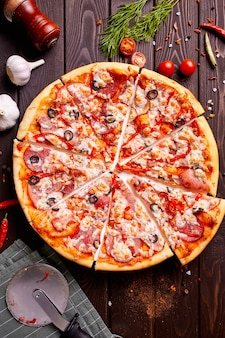 Fresh pizza with tomatoes, cheese and mushrooms on wooden table closeup.