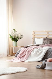 Fresh plants in ceramic vase standing on bedside table in white bedroom interior with window with curtains, king-size bed and white fluffy rug on the floor