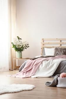 흰색 침실 인테리어의 침대 옆 탁자에 서 있는 세라믹 꽃병에 든 신선한 식물, 커튼이 있는 창문, 킹 사이즈 침대, 바닥에 흰색 푹신한 깔개