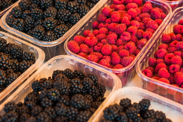 Fresh plastic transparent crate filled with raspberries and blackberries