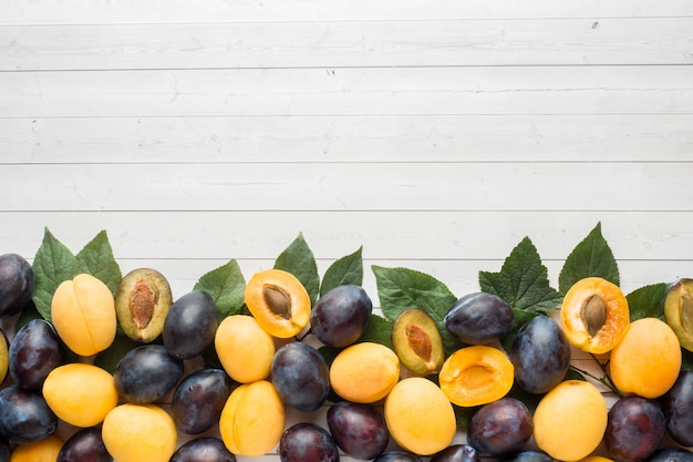 Fresh plum and apricot berries with leaves on a light table background
