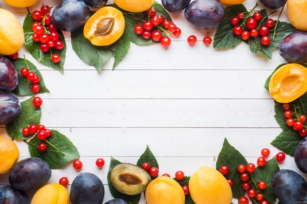 Fresh plum, apricot and red currant berries with leaves on a light table. background copyspace