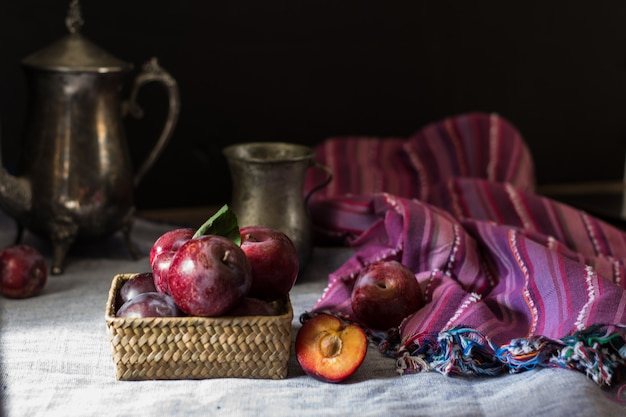 Fresh plum. autumn harvest. red plums. yellow plum. napkin and vintage kettle and glass. b