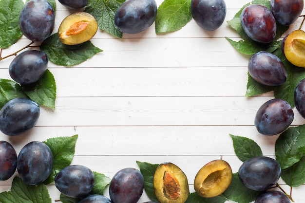 Fresh plum fruit with leaves frame on a light table background