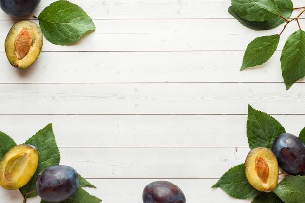Fresh plum fruit with leaves on a light table. background copyspace