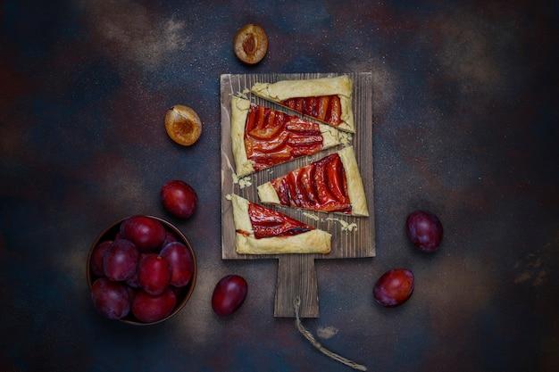 Fresh plum galette pie with raw plums on dark