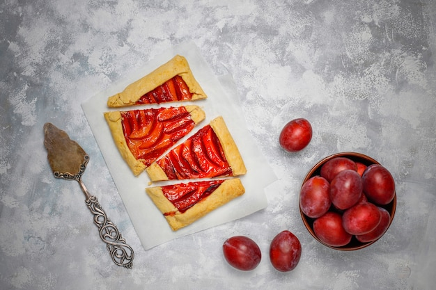 Fresh plum galette pie with raw plums on dark