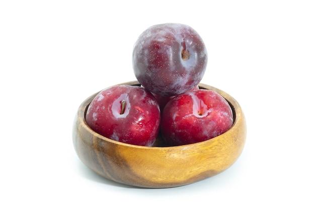 背景に木製のボウルに新鮮な梅、健康食品。ジュリープラム。
