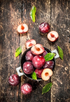 Fresh plums in a bowl. on a wooden background.