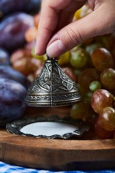 Prugne fresche, un grappolo d'uva e sale su tavola di legno.
