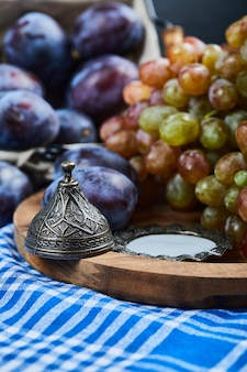 Fresh plums and a bunch of grapes on tablecloth.