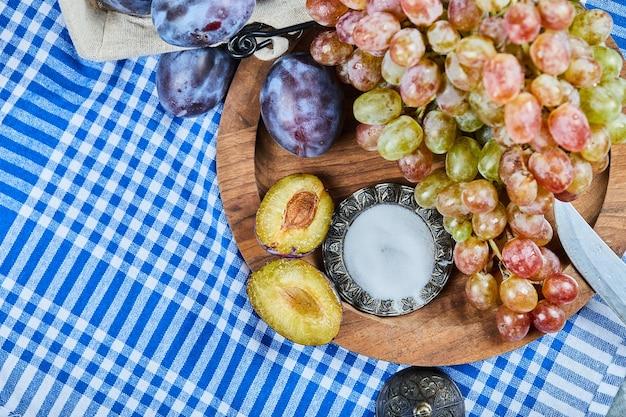 Prugne fresche e un grappolo d'uva sul piatto di legno.