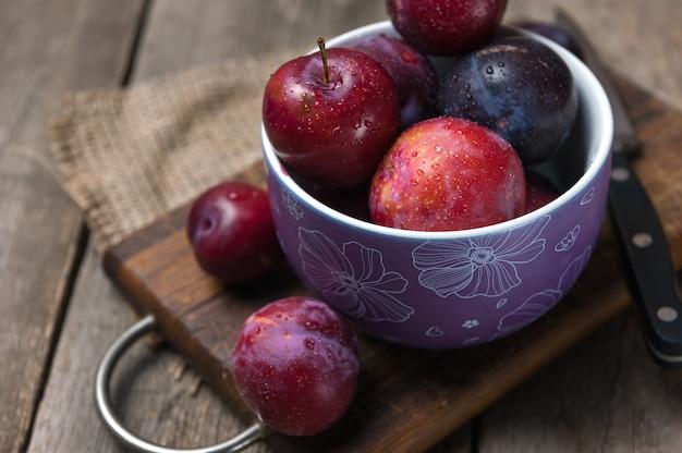 木製のテーブルに紫のボウルに新鮮な梅