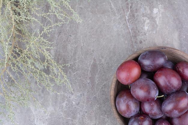 石の背景に木製のボウルに新鮮な梅。