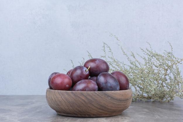 Свежие сливы в деревянной миске на каменном столе.