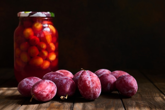 Fresh plums and a jar of plum compote on a dark wooden table, selective focus on the central plum, shallow depth of field Premium Photo