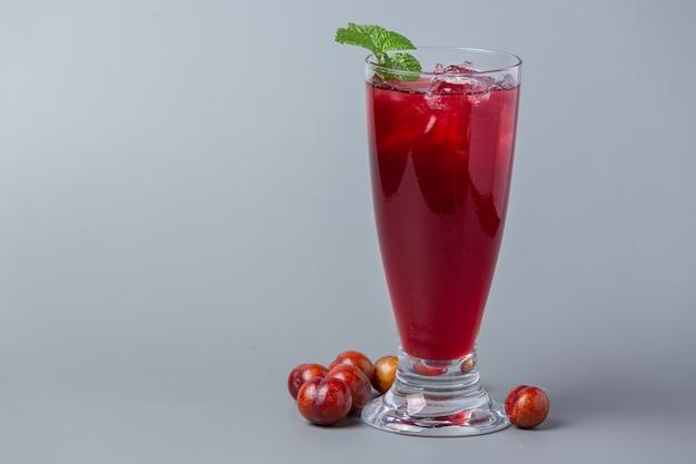 Свежий сливовый сок на серой поверхности.