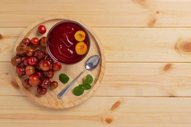 Succo di prugne fresco sulla superficie in legno.