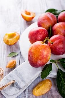Fresh plums on marble cutting board