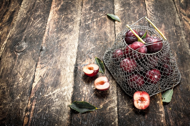 Fresh plums in a mesh bag. on a wooden background.