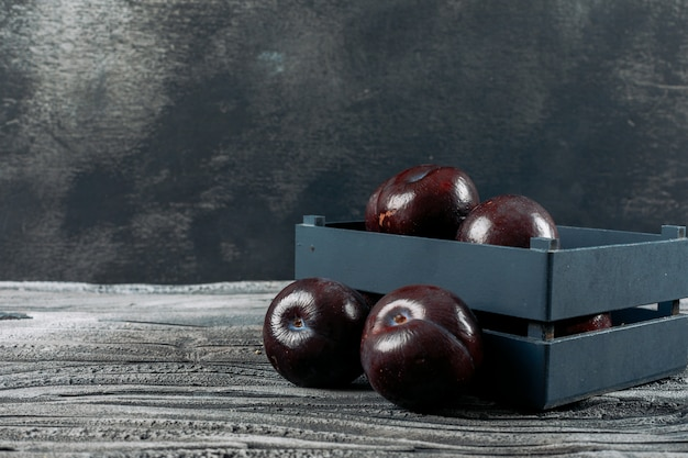 Fresh plums in a plate on a dark grey background. side view.