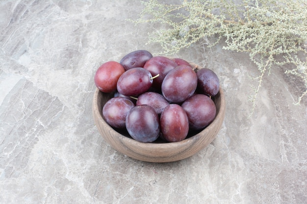 Fresh plums in wooden bowl on stone background.