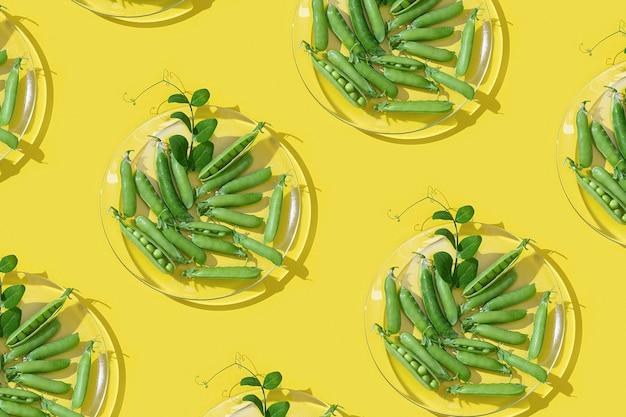 노란색 바탕에 유리 접시에 신선한 잎 녹색 완두콩의 신선한 포드 프리미엄 사진