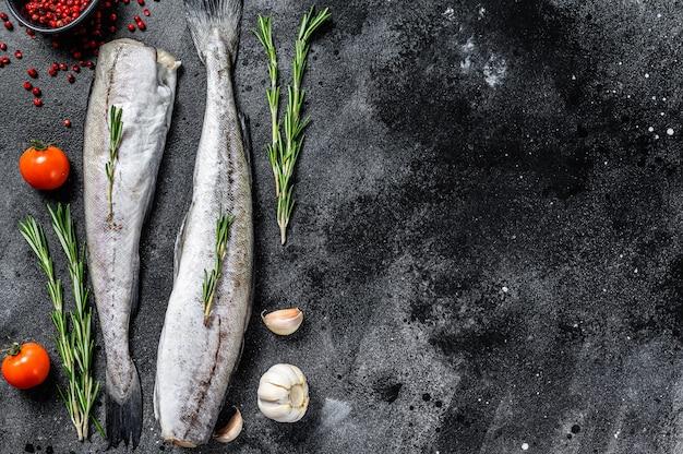 Свежая рыба минтая. сырые морепродукты. черный фон. вид сверху. скопируйте пространство.