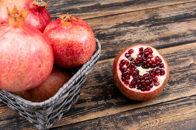 Fresh pomegranate in basket top view on wooden table